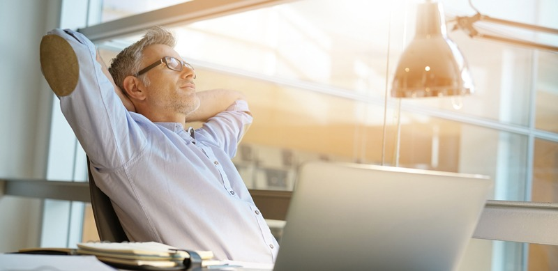 Man leaning back in chair in front of laptop